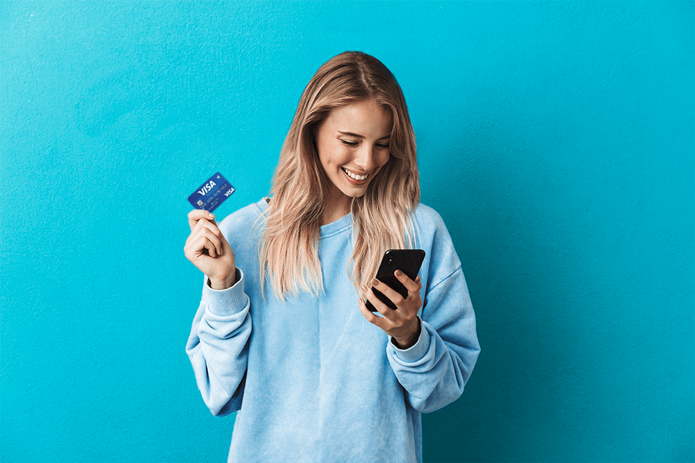 young smiling blond woman dressed in blue jumper holding debit card in right hand and phone in left hand